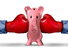 Financial money pressure and money crunch business concept with two red boxing gloves putting the squeeze on a pink piggy bank under a finance crisis pressure as an icon of savings and budget problems.